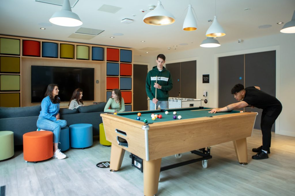 A group of people socialising around a pool table
