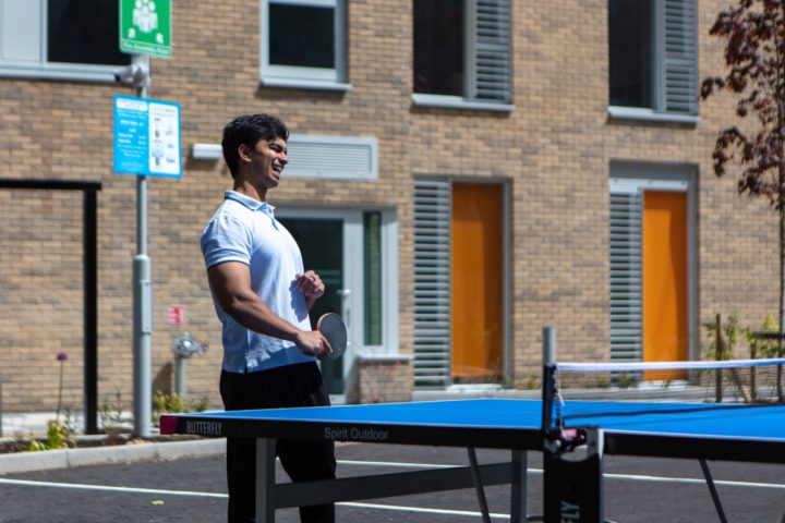 A person playing table tennis outside