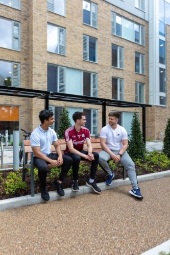 Three people sat outside, in front of a building